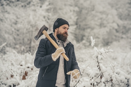 Temperature, freezing, cold snap, snowfall. Bearded man with axe in snowy forest. skincare and beard care in winter, beard warm in winter. Man lumberjack with ax. Camping, traveling and winter rest. Stock Photo