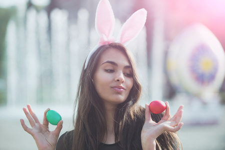Cheerful girl or cute woman with rosy bunny ears and long, brunette hair posing with colored eggs, green and red, in hands on sunny day on blurred natural background. Easter. Spring 版權商用圖片