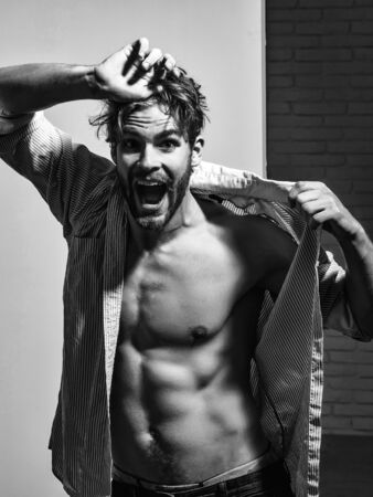 Angry handsome man with beard or blond muscular macho athlete bodybuilder in unbutton shirt shows six packs and abs on muscle torso on white background