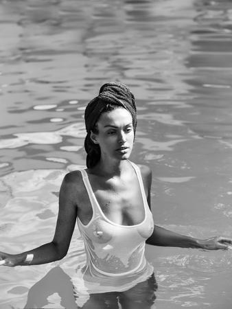 かわいい顔とテリータオルを持つ若いセクシーな女性や女の子は、裸の胸と濡れた白いベストで青い水晴れた夏の日屋外でプールで泳ぐ髪に 写真素材