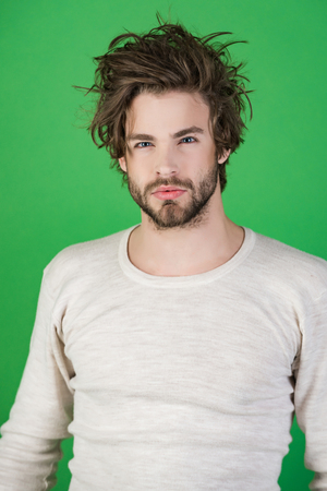 Barber and hairdresser, male fashion. Insomnia, energy, single with uncombed hair. Man with disheveled hair in underwear. Sleepy man with beard on green background. Morning wake up, everyday life.
