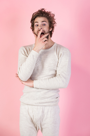 Morning wake up, everyday life. Barber and hairdresser, male fashion. Man with disheveled hair in underwear. Insomnia, energy, single with uncombed hair. Sleepy man with beard on pink background.