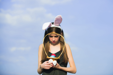 Easter woman holding wicker basket with colored eggs. Unhappy girl with rosy bunny ears on blue sky. Fertility and rebirth concept. Easter tradition and symbol. Spring and holiday celebration
