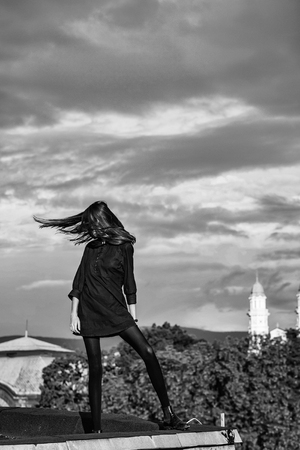 Pretty girl young beautiful woman with brunette hair in sexy black dress on roof on cloudy blue sky Reklamní fotografie