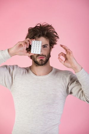 Man with pills in blister pack. Health and medicine, hangover. Cold, flu and headache treatment, hypnotic tablet. Dieting pill and vitamin, man with anabolic. Drug and antidepressant, insomnia. Stock Photo