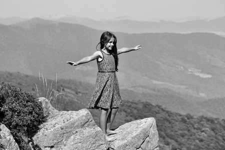One brunette smiling girl in blue lace dress standing with raised hands on stone rock cliff looking at beautiful landscape sunny day outdoor on natural blue sky background, horizontal photo Banco de Imagens