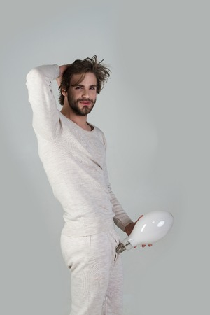 Solution and decision, big size. penis enlargement. Energy and electricity. Man with disheveled hair hold big lamp. Power? business success. Happy guy has an idea on grey background, morning, potency