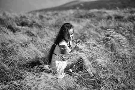 Small pretty brunette girl in white lace summer dress sitting in mountain valley among deep dry spikelet grass in spring sunny day outdoor on natural background, horizontal picture