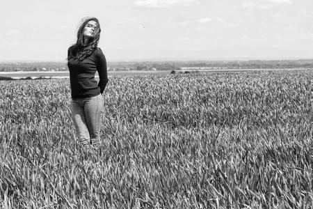 젊은 섹시 한 여자 또는 여자 갈색 머리 머리와 예쁜 얼굴에 검은 카디 건과 청바지 흐린 푸른 하늘 필드에 녹색 잔디 자연 백그라운드 복사 공간