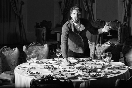 Surprised man handsome young male with beard and blond hair eats vegetables with wine in glass from dirty plates with leftovers or residues of food after banquet dinner on table in restaurant Reklamní fotografie