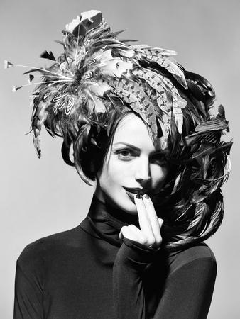 灰色の背景にハロウィーンやカーニバルの休日の衣装として美しい羽の帽子茶色の色できれいな顔に赤い唇を持つ若いセクシーな女性や女の子