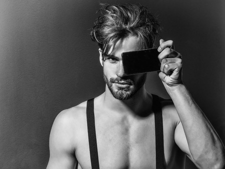 Handsome man confident fashion sexy young blond bearded male model with suspenders on topless sexi nude torso hides face behind smartphone or mobile phone on grey background Banco de Imagens