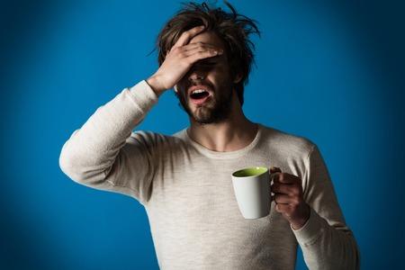 Rhume et grippe, célibataire. Un gars endormi avec une tasse de thé a des maux de tête sur fond bleu. Matin avec du café ou du lait. Un homme aux cheveux ébouriffés boit du vin chaud. Insomnie, rafraîchissement et énergie. Banque d'images - 94150668