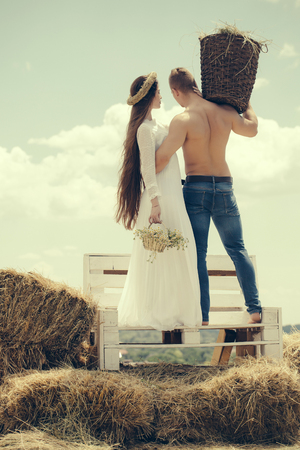 Couple in love hug on bench on grey sky. Woman with long hair in white dress with flowers. Summer vacation concept. Man with muscular torso hold wicker basket. Romance, relationship, relations.