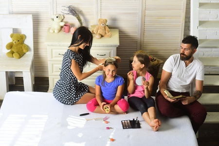Family and fashion concept. Family sits in stylish bedroom. Dad with beard reads, mom makes her daughter hairstyle, girls do makeup. Man with tattoo, woman with long hair and kids with smiling faces.