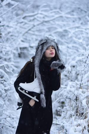 Vacation, holidays, hobby, lifestyle. Woman with skating shoes in winter clothes in snowy forest. Ice skating concept. Sport, activity, health. Girl with pair of figure skates at trees in snow. Stock Photo
