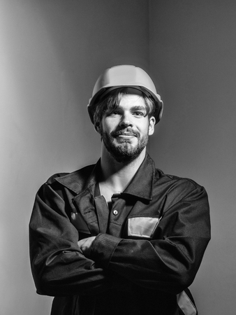 Handsome man builder construction mason worker repairman craftsman foreman in orange hard hat and boilersuit stands with arms crossed on grey background