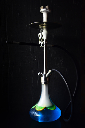 Hookah of glass and metal on dark background. Shisha, sheesha, nargile, hubbly bubbly. Smoking, bad habits, addiction.