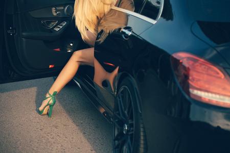 Zakenreis of commandant, callgirl. Onderneemster of mooi meisje in auto. Jonge vrouw stap uit auto met sexy been. Reizen en vakantie. Modern leven, luxe, stad, glamour. Stockfoto