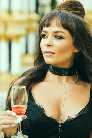Girl with long brunette hair in black lace bustier. Woman holding glass of wine outdoors. Cocktail party or holiday celebration. Drinking alcohol concept. Bad habit and addiction. Stock Photo