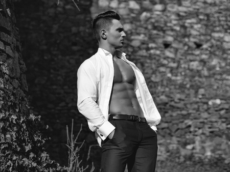 Man half face bare-chested young handsome sensual model in white shirt gaped open poses with hands in black trouser pockets outside on masonry background