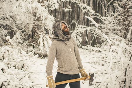 bearded man lumberjack hold axe in snowy winter forest at christmas holiday, winter sport and rest, holiday and vacation, camping and traveling, freezing