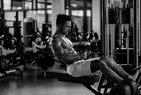 Handsome young man with sexy muscular wet body and bare chest training with heavy exercise equipment in gym