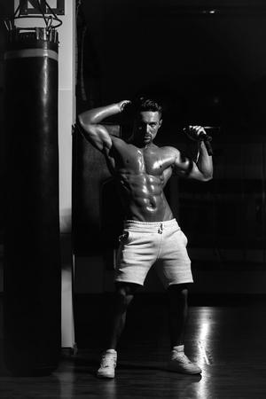 Knappe jonge man met sexy gespierde nat lichaam naakte torso en borst houden springtouw Stockfoto - 94304096