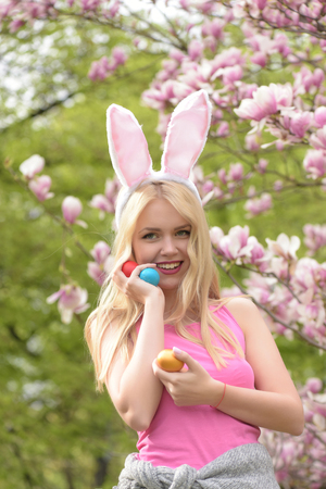 easter woman with eggs in bunny ears at magnolia, Spring. Easter. Holidays, celebration