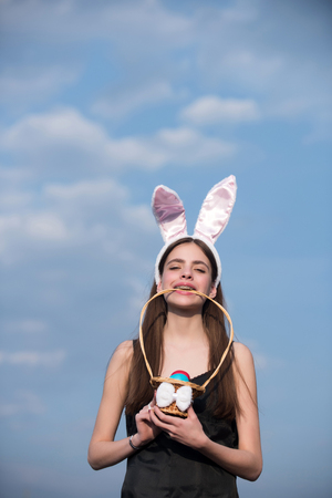 Easter girl with bunny ears and eggs on blue sky. Woman holding wicker basket in teeth on sunny day. Easter tradition and symbol. Fertility and rebirth concept. Spring holiday celebration