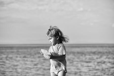 Mignon bébé enfant avec des cheveux blonds bouclés en chemise verte joue avec de la pierre à la plage de mer sur la journée d & # 39 ; été Banque d'images - 94115223