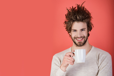 Man with disheveled hair drink mulled wine. Insomnia, refreshment and energy. Morning with coffee or milk. Happy guy with tea cup on red background. Cold and flu, single, copy space 免版税图像