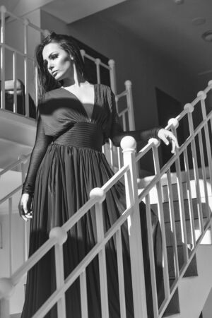 Young beautiful woman with brunette hair in elegant red dress on stairs