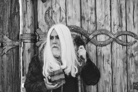 長い灰色の髪と鉄の装飾と木製の背景に屋外で木製のマグカップで深刻な顔にひげを持つドルイド老人