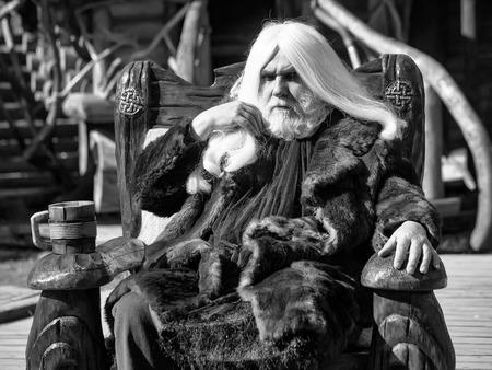 毛皮のコートに長い銀髪のひげを持つドルイド老人は、ぼやけた背景に木製のマグカップで椅子に座っています 写真素材