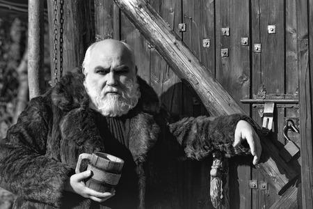 木製の背景に屋外の毛皮のコートで鉄の装飾と木製のカップを保持する深刻な顔に長いひげを持つひげの男