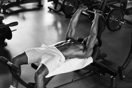 Knappe jonge man met sexy gespierde natte lichaam naakte torso en borsttraining met zware barbell in de sportschool Stockfoto - 93987627