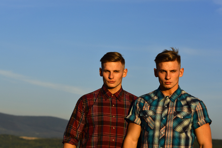 Men twins in sunset or sunrise, friendship. Men twins with athletic body, family values, copy space