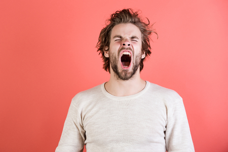 Sleepy man with beard on red background. Insomnia, energy, single with uncombed hair. Morning wake up, everyday life. Barber and hairdresser, male fashion. Man with disheveled hair yawn in underwear. Imagens - 94043375