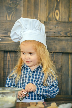 Boy baker in chef hat with cookie cutter. Dough and kitchen utensils on wooden table. Playing and learning. Homemade cooking and baking. Happy childhood concept.