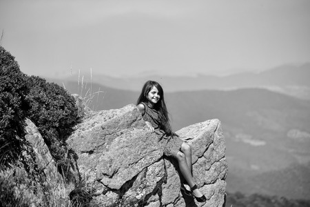 Beautiful brunette smiling girl touching long hair in blue lace dress sitting on stone rock cliff looking at beautiful landscape sunny day outdoor on natural blue sky background, horizontal