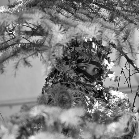 青い目をした若い女の子兵士のディフェンダーは、スプルースの木の背景に立って銃を持つギリー迷彩軍弾でマスクで閉じました