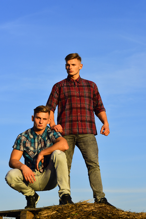 Two young male twins with muscular torso on blue sky Stock Photo