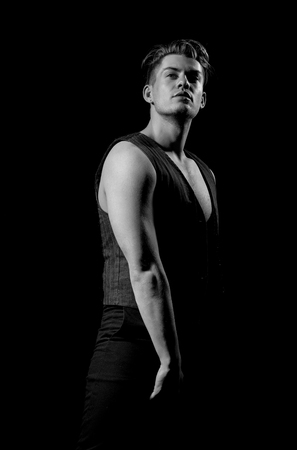 Handsome man or young caucasian macho, athlete, bodybuilder, with stylish haircut, hair, posing in unbutton vest with muscular torso, hands, arms, with biceps, triceps on black background Stock Photo