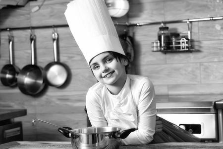Petite fille avec pan dans le chapeau de cuisinier. Cuisine, nourriture, étude Banque d'images - 94043581