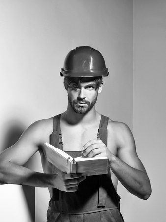 Handsome man builder repairman craftsman foreman or construction worker in orange hard hat and overall keeps accounting book on grey background Reklamní fotografie