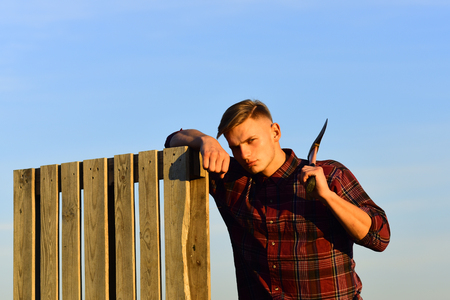 man holds axe with serious face on blue sky background