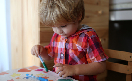 Education and hobby. Childhood and happiness, learning. Painter child with coloring book. Kid or blonde happy boy paint with felt pen. Small boy child drawing with colorful marker pen. art, creativity
