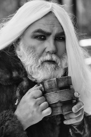 ぼやけた背景に手に木製のマグカップを持つ長い銀のひげと髪のしわを持つドルイド老人