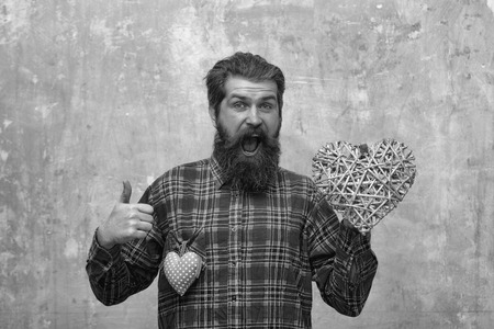 Bearded happy man, caucasian hipster, with long beard and moustache in plaid shirt with two hearts, wicker and rosy textile, love gifts for valentines day, on beige grunge wall background 版權商用圖片 - 94518349